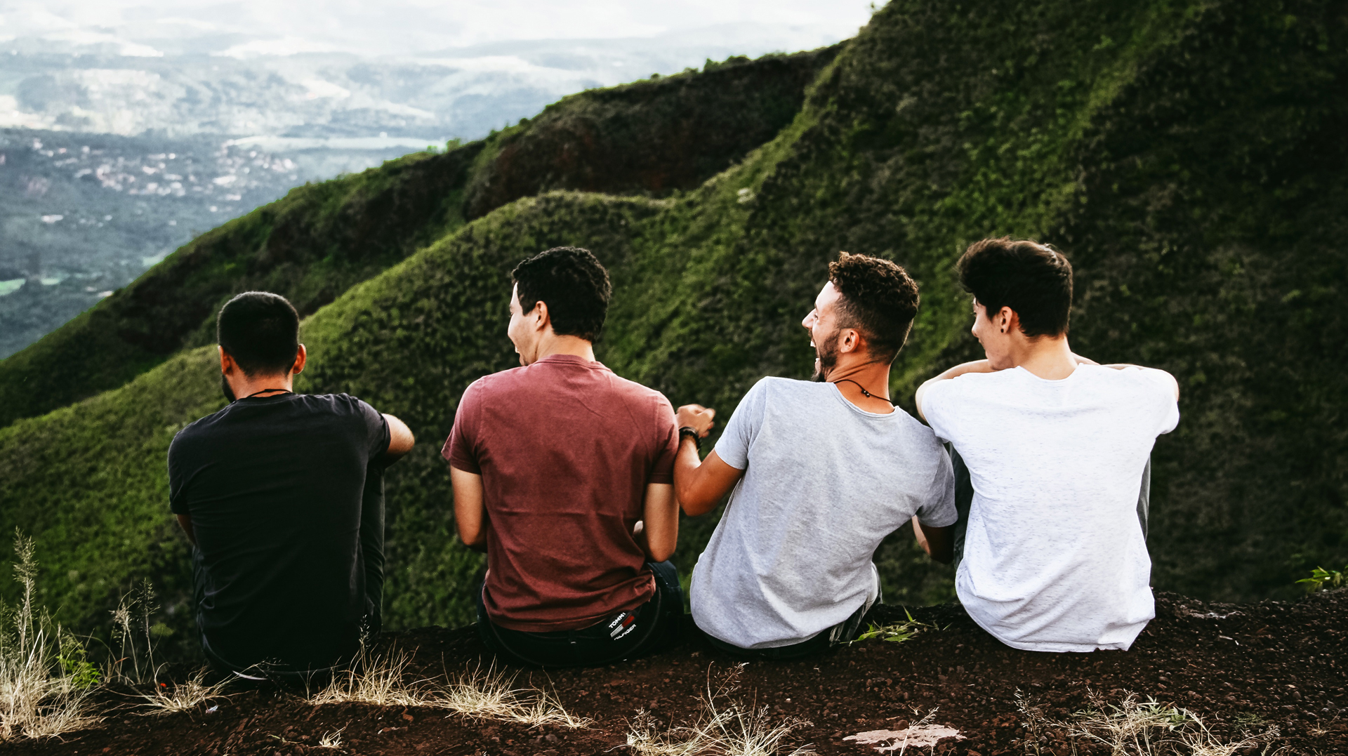 Four guys laugh while sitting on a ledge overlooking a valley