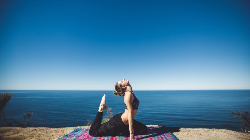 Photo of a girl in activewear doing yoga on a headland in Sydney body