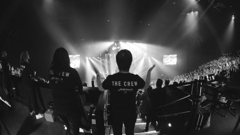 A volunteer team member at Presence Conference 2017 stands with hands lifted in worship at the ICC Sydney