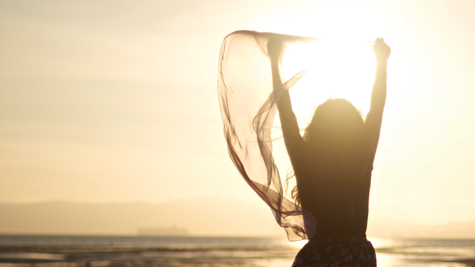 A woman holds her hands in victory while overlooking an ocean