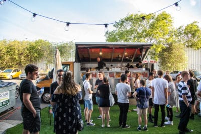 Young people stand and talk outside at C3 Rozelle next to a mobile taco truck.