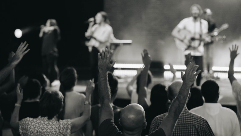 A man lifts his hands in worship at C3 Church Oxford Falls to receive healing during a service