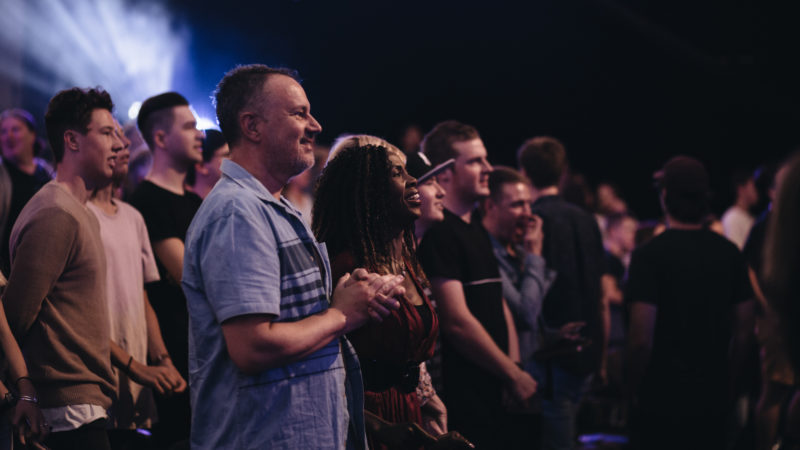Mixed race couple at Night of Worship smile at audience no divide division