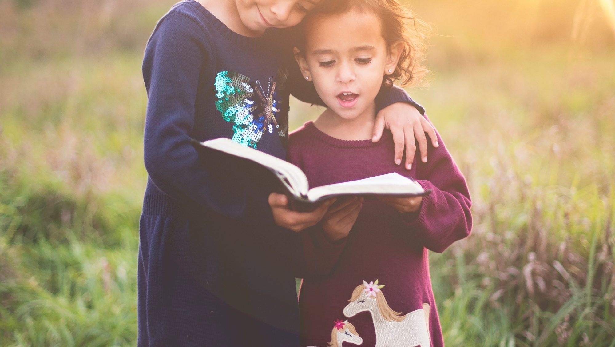 Two girls read scripture from the Bible in a field