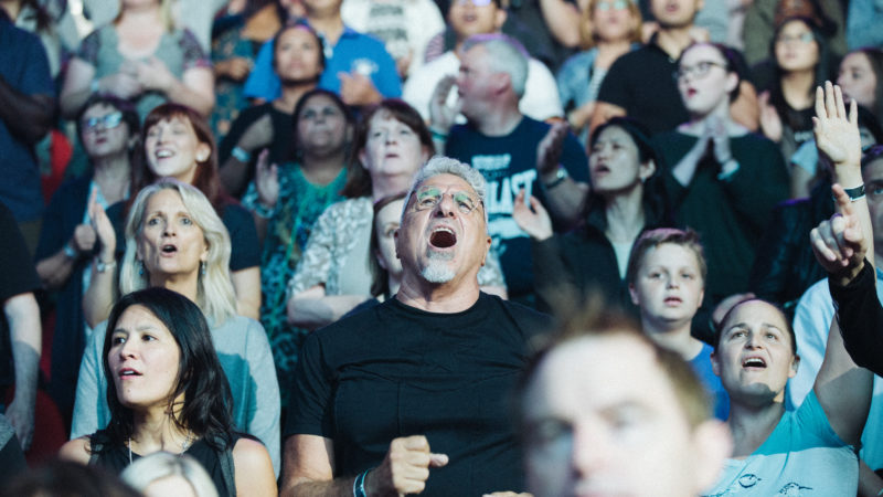 Man in worship at Presence Conference sings with his mouth open experiencing freedom