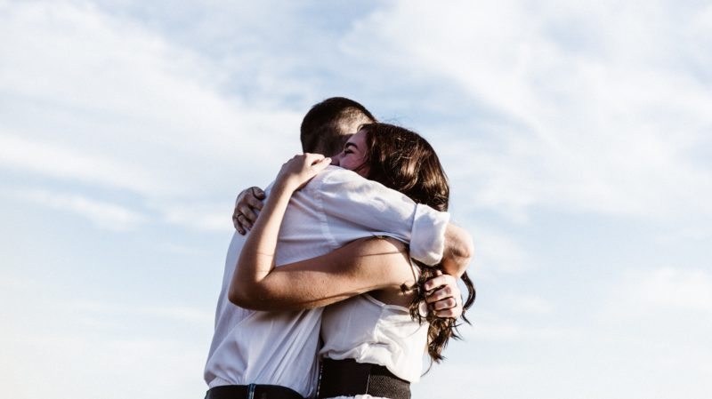 A man and woman embrace with a blue sky behind them