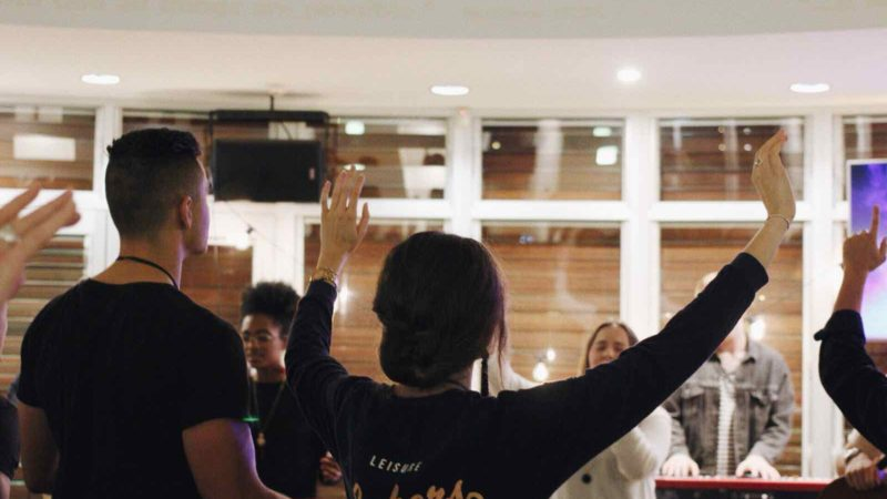 Young woman lifts hands in worship at C3 Young Adults Oxford Falls Service